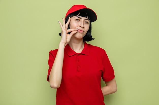 Zufriedene junge kaukasische lieferfrau, die ihren mund verschließt