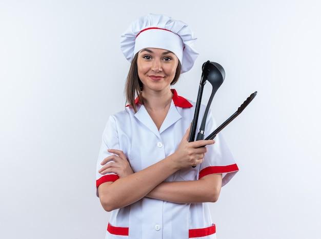 Zufriedene junge köchin mit kochuniform, die die hände kreuzt, die pfannenwender mit schöpfkelle halten, isoliert auf weißer wand