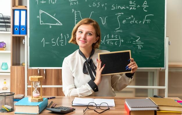 Zufriedene junge lehrerin sitzt am tisch mit schulwerkzeugen, die eine mini-tafel im klassenzimmer halten