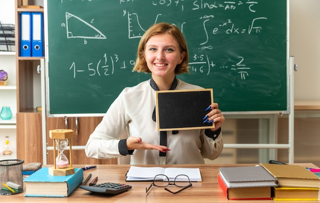 Zufriedene junge lehrerin sitzt am tisch mit schulwerkzeugen und zeigt mit der hand auf die mini-tafel im klassenzimmer