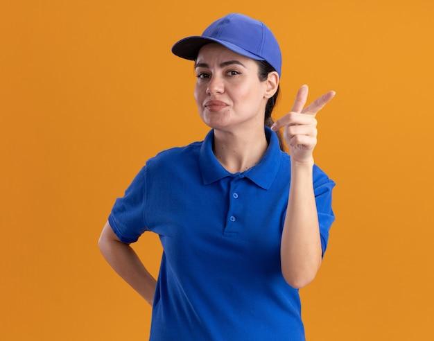 Zufriedene junge lieferfrau in uniform und mütze, die die hand hinter dem rücken hält und auf die kamera zeigt, die auf orangefarbener wand isoliert ist?