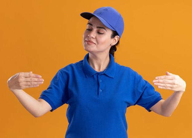 Zufriedene junge lieferfrau in uniform und mütze tut so, als ob sie etwas vor ihr hält und es isoliert auf oranger wand betrachtet