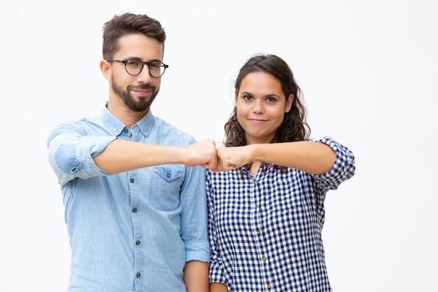 Zufriedene junge paare, die fäuste berühren