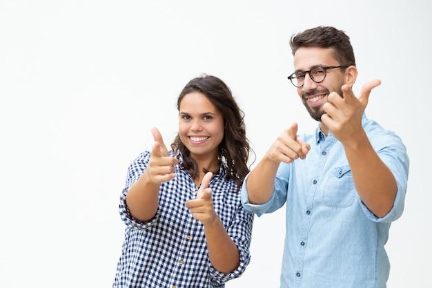 Zufriedene junge paare, die fingergewehre zeigen