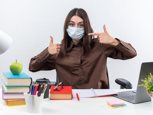 Zufriedene junge schulfrau mit medizinischer maske sitzt am tisch mit schulwerkzeugen, die den daumen nach oben zeigen