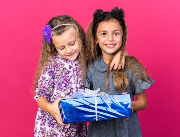 Zufriedene kleine hübsche mädchen, die geschenkbox zusammenhalten, isoliert auf rosa wand mit kopierraum