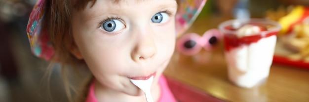 Zufriedene kleine kind leckt löffel mit eis