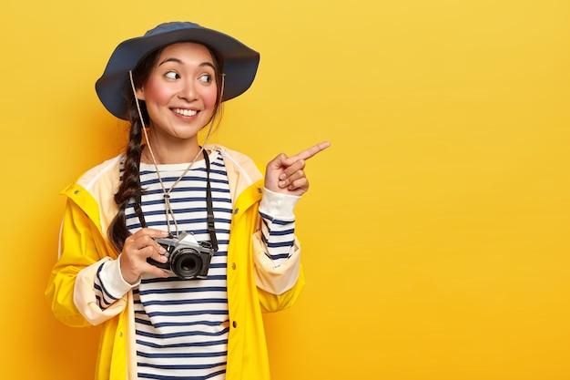 Zufriedene koreanische frau trägt kopfbedeckung, gestreiften pullover und gelben regenmantel, zeigt mit dem zeigefinger zur seite, fördert den kopierraum, trägt eine retro-kamera, reist an einem wilden ort, hat eine fantastische expedition