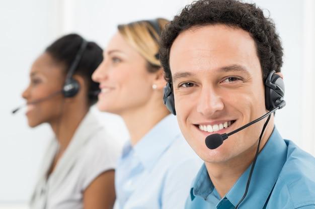 Zufriedene kunden mit headsets, die mit anderen kollegen im call center zusammenarbeiten