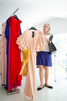 Zufriedene kundin, die kleiderbügel mit kleid am gestell hält und stoff zum ausprobieren nimmt. frau, die kleidung im modegeschäft wählt. einkaufs- oder einzelhandelskonzept