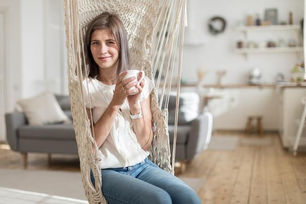 Zufriedene lächelnde frau, die becher beim sitzen im rustikalen umsponnenen schwingenstuhl im sonnigen wohnzimmer hält