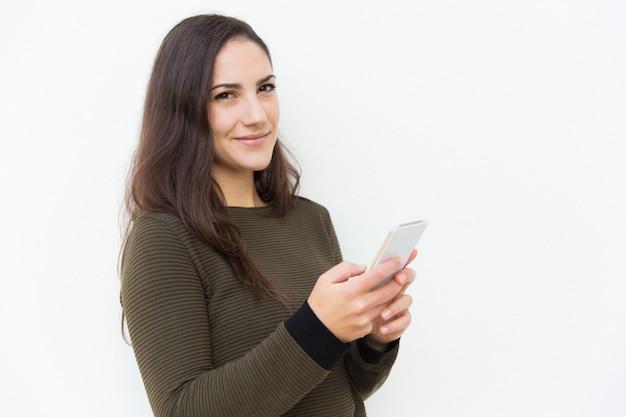Zufriedene lächelnde lateinische frau, die mobiltelefon hält