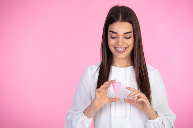 Zufriedene lockige frau berührt menstruationstasse mit vergnügen, steht mit flexibler menstruationstasse
