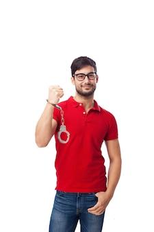 Zufriedene mann mit handschellen an seinem handgelenk