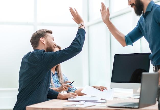 Zufriedene mitarbeiter, die sich am arbeitsplatz im büro gegenseitig einen high five geben