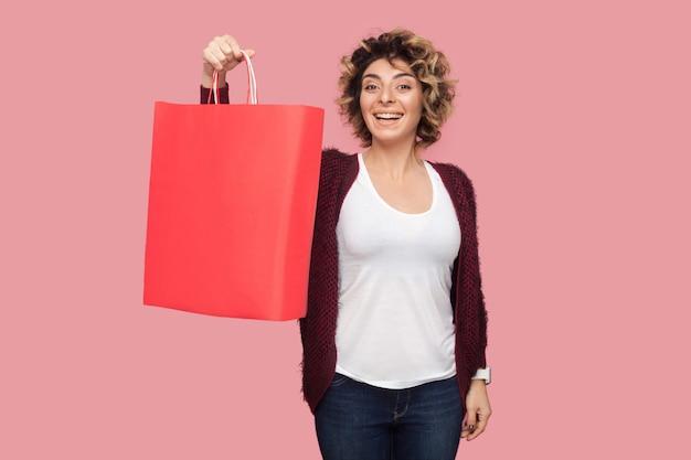 Zufriedene moderne junge frau in blauem hemd mit lockiger frisur, die einkaufstaschen und ein zahniges lächeln zeigt und in die kamera schaut. studioaufnahme, rosa hintergrund, isoliert, innenbereich, kopienraum