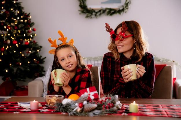 Zufriedene mutter in rentierbrille mit blick auf tochter mit tasse am tisch sitzend die weihnachtszeit zu hause genießen