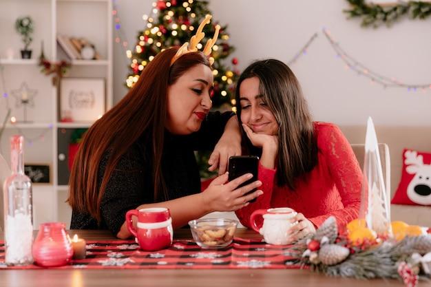 Zufriedene mutter mit rentierstirnband und tochter schauen auf das telefon, das am tisch sitzt und die weihnachtszeit zu hause genießt