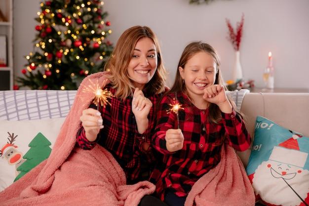 Zufriedene mutter und tochter, die mit decke bedeckte wunderkerzen halten und betrachten, die auf der couch sitzen und die weihnachtszeit zu hause genießen