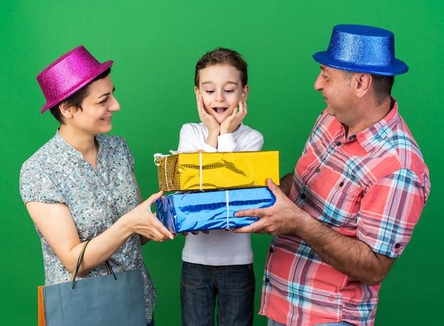 Zufriedene mutter und vater mit partyhüten, die geschenkboxen halten und ihren überraschten sohn zusammen isoliert auf grüner wand mit kopierraum betrachten