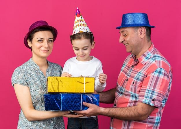 Zufriedene mutter und vater mit partyhüten, die geschenkboxen zusammenhalten, die mit ihrem sohn isoliert auf rosa wand mit kopierraum stehen