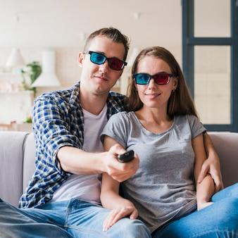 Zufriedene paare, die auf sofa sitzen und film genießen