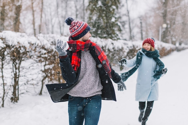 Zufriedene paare, die schneebälle im park spielen
