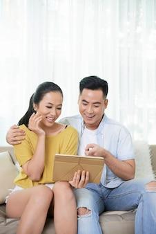 Zufriedene paare, die tablette aufpassen und lachen