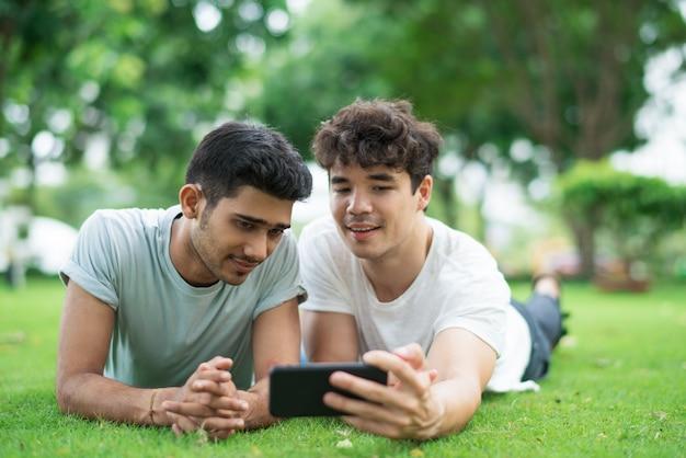 Zufriedene paare von den männern, die für selfie auf smartphone aufwerfen