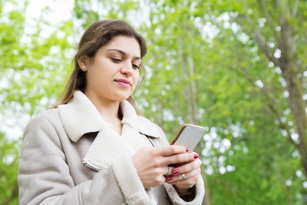 Zufriedene recht junge frau, die smartphone im park verwendet