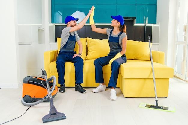 Zufriedene reinigungskräfte in blauen uniformen, die sich gegenseitig hohe fünf geben und den boden in der küche weiter reinigen.
