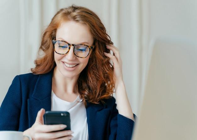 Zufriedene rothaarige frau verwendet ein modernes elektronisches gerät zum überprüfen von newsfeed, online-kommunikation und suchen von informationen, sitzt im coworking space, verwendet eine hochgeschwindigkeits-internetverbindung.