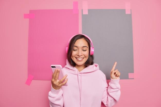 Zufriedene tausendjährige asiatische frau macht videoanrufe, die auf etwas hinweisen, das bei leerzeichen lächelt, zeigt angenehm die richtung des verkaufslogo-ladenbanners trägt hoodie-posen gegen rosa wand