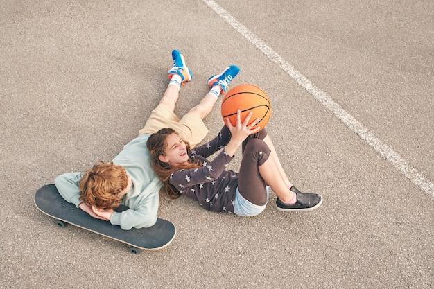 Zufriedene teenager-freunde, die mit skateboard und basketball auf der straße liegen