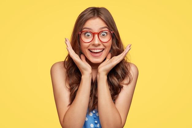Zufriedene überglückliche junge frau mit brille gegen die gelbe wand posierend