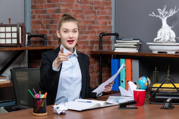 Zufriedene und positive junge dame, die an einem tisch sitzt und das dokument nach vorne im büro hält