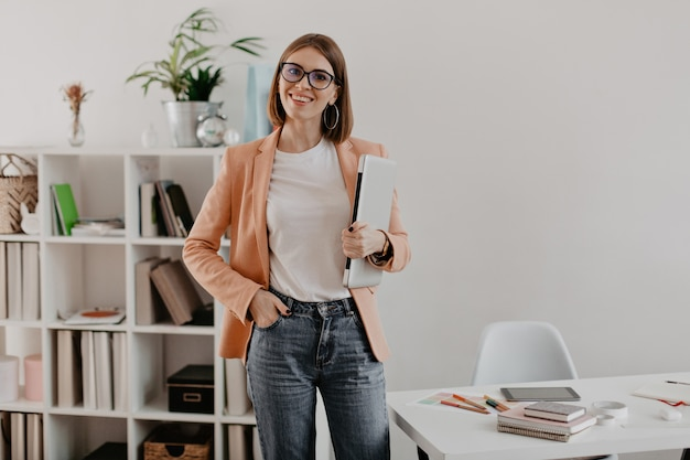 Zufriedene unternehmerin posiert mit laptop in der hand gegen ihr minimalistisches büro.
