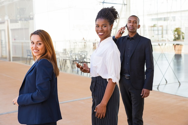 Zufriedene unternehmungslustige multiethnische geschäftsleute in der lobby
