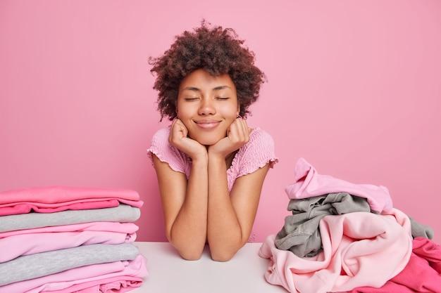 Zufriedene verträumte hausfrau lehnt sich mit stapeln sauberer kleidung am tisch, hält die hände unter den kinnaugen geschlossen und macht pause, nachdem sie wäsche einzeln über rosafarbener wand gefaltet hat. konzept der hausarbeit
