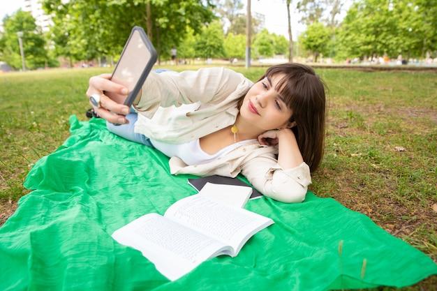 Zufriedene weibliche frau, die smartphone im park verwendet