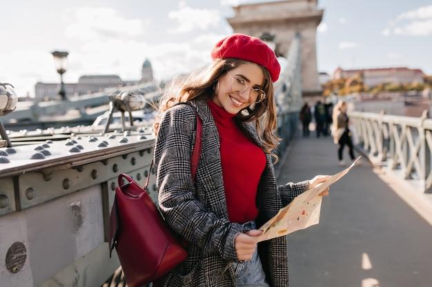 Zufriedene weibliche reisende im eleganten outfit, das urlaub in frankreich verbringt