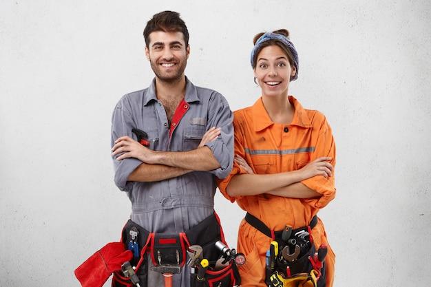 Zufriedene weibliche und männliche techniker in spezieller uniform halten die hände gefaltet, während sie auf anweisungen des arbeitsaufsehers oder vorarbeiters warten