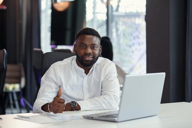 Zufriedener afroamerikaner-büroleiter arbeitet am laptop lächelnd und erhoben daumen.