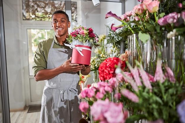 Zufriedener afroamerikanischer blumenladenangestellter, der mit einer blumenkomposition in seinen armen in die kamera lächelt