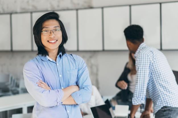 Zufriedener asiatischer student mit langen haaren, der in selbstbewusster haltung im hörsaal steht. porträt von der rückseite des afrikanischen kerls, der mit universitätskameraden spricht, während erfolgreicher chinesischer junger mann mit lächeln aufwirft.
