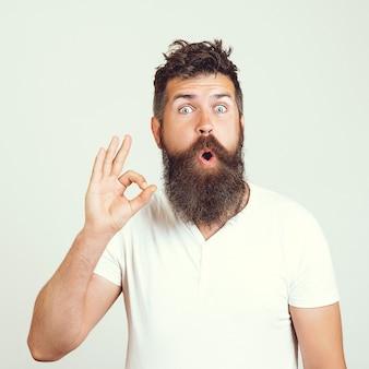 Zufriedener bärtiger männlicher hipster zeigt ok zeichen, zeigt seine zustimmung, beweist, dass alles wunderbar ist. körpersprachenkonzept, zeigt ok. präsentieren sie ihr produkt. ausdrucksstarke mimik