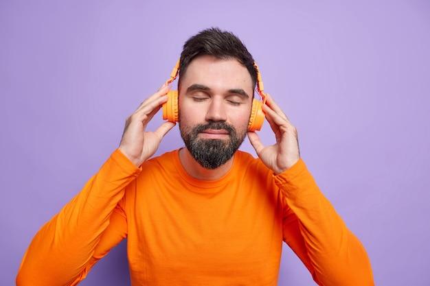 Zufriedener bärtiger mann ruht mit musik trägt stereo-kopfhörer auf den ohren hört lieblings-playlist hält die augen geschlossen trägt leuchtend orangefarbenen pullover