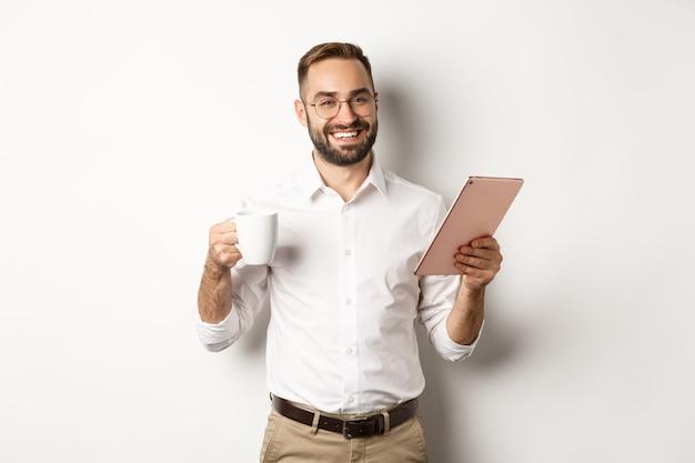 Zufriedener chef trinkt tee und benutzt digitales tablet, liest oder arbeitet, steht