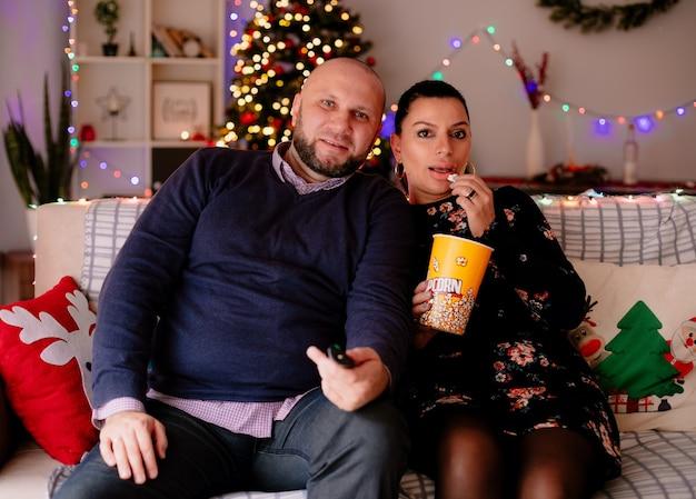 Zufriedener ehemann und ehefrau zu hause in der weihnachtszeit sitzen auf dem sofa im wohnzimmer ehemann hält fernbedienung frau hält popcorn-eimer und isst popcorn, die beide fernsehen