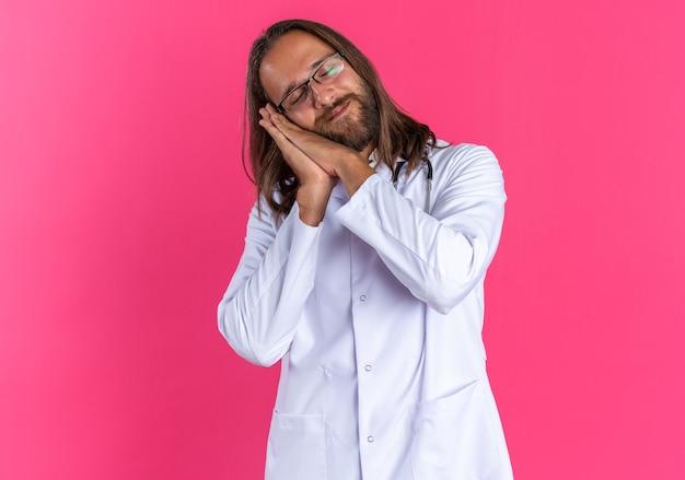 Zufriedener erwachsener männlicher arzt, der medizinische robe und stethoskop mit brille trägt und mit geschlossenen augen schlafgeste macht